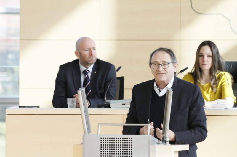 Der Abgeordnete mit Brille am Rednerpult des schleswig-holsteinischen Landtags
